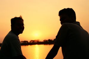 Image of friends talking by a sunset.